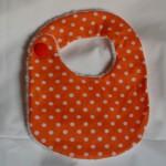 Bavoir à pois blancs sur fond orange, doublé de tissu éponge blanc, 100% coton, fermé par un gros bouton. Lavage 30° en machine.