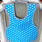 Bavoir à manches, 100% coton, à petites étoiles blanches sur fond turquoise, doublé de tissu éponge blanc, attaches à nouer. Lavage 30° en machine.