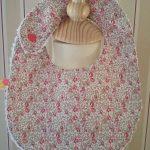 Bavoir Liberty Eloise rose 100% coton, doublé de tissu éponge blanc. Attache par pression. Dimensions : 21x27cm. Lavable 30° en machine.