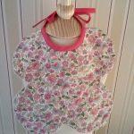 Bavoir à petites fleurs roses, forme papillon, 100% coton, doublé de tissu éponge blanc. Attaches à nouer. Dimensions : 24x24 cm. Lavable 40° en machine.