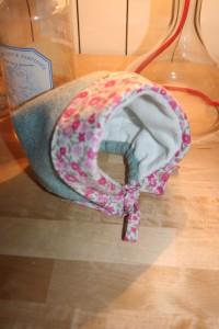 Petit béguin 6 mois en laine bleu ciel chiné. Intérieur en tissu doudou blanc à poils ras bien chaud. Revers du béguin en coton style Liberty à petites fleurs roses. Lavage 30° en machine.