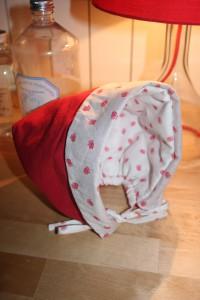 Petit béguin taille 12 mois en velours milleraies rouge 100% coton. Intérieur en tissu coton à petites fraises. Doublure en ouatine légère pour plus de chaleur. Lavage 30° en machine. Ne pas repasser le velours sur l'endroit.