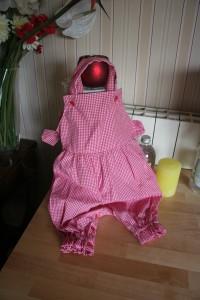 Salopette bébé taille 12 mois en vichy rouge. Bretelles croisées sur le dos et attachées par de petits boutons sur le devant. Ouverture au niveau de l'entrejambe fermée par les mêmes petits boutons que sur le haut du vêtement. Petits nœuds décoratifs de chaque côté.