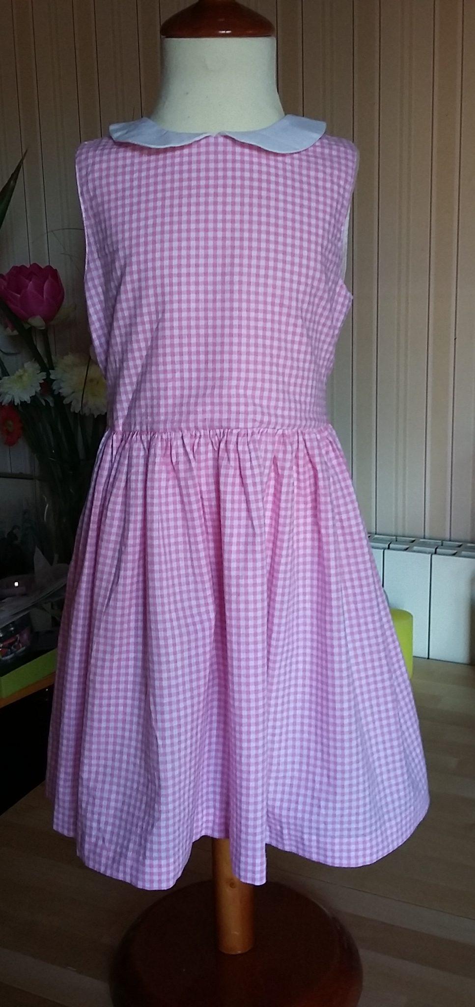 Robe 100% coton en vichy rose. Taille 4 ans. Col contrastant en piqué de coton blanc. Ceinture en coton blanc également. Petits boutons roses.