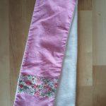 Écharpe en velours milleraies rose (coton) avec bande de Liberty D'Anjo rose à chaque bout sur le recto. Verso en tissu doudou blanc agrémenté d'un passant permettant de maintenir l'écharpe serrée. Dimensions : 65 x 10 cm environ. Lavage 30° en machine. Ne pas repasser le velours sur l'endroit.