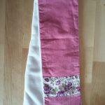 Écharpe en velours milleraies rose foncé (coton) avec bande de Liberty Felicité prune à chaque bout sur le recto. Verso en tissu doudou blanc agrémenté d'un passant permettant de maintenir l'écharpe serrée. Dimensions : 65 x 10 cm environ. Lavage 30° en machine. Ne pas repasser le velours sur l'endroit.