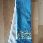 Écharpe en velours milleraies turquoise (coton) avec bande de Liberty Eloise bleu et vert à chaque bout sur le recto. Verso en tissu doudou blanc agrémenté d'un passant permettant de maintenir l'écharpe serrée. Dimensions : 65 x 10 cm environ. Lavage 30° en machine. Ne pas repasser le velours sur l'endroit.