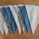 Guirlande de 8 fanions (15x19cm) dans les tons bleus. Fanions 100% coton. Les fanions sont reliés par un biais argenté (lurex) de 2m. Lavage machine 30°. Repassage fer doux (ne pas repasser le biais).
